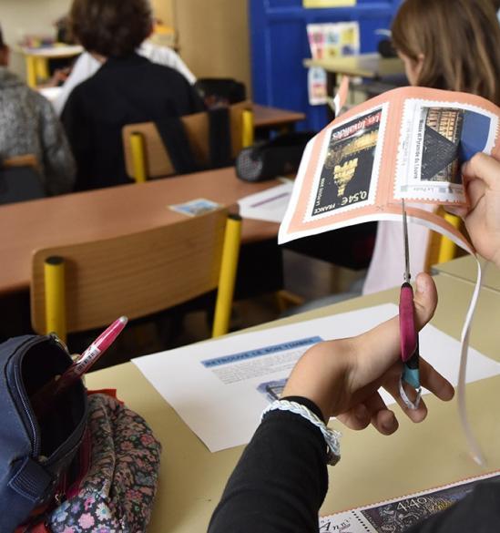 Atelier jeune public, petite fille découpant des timbres