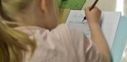 Atelier jeune public, enfant entrain d'écrire à l'encre noir