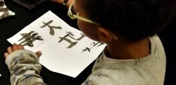 Atelier jeune public, enfant entrain d'écrire à l'encre chinoise